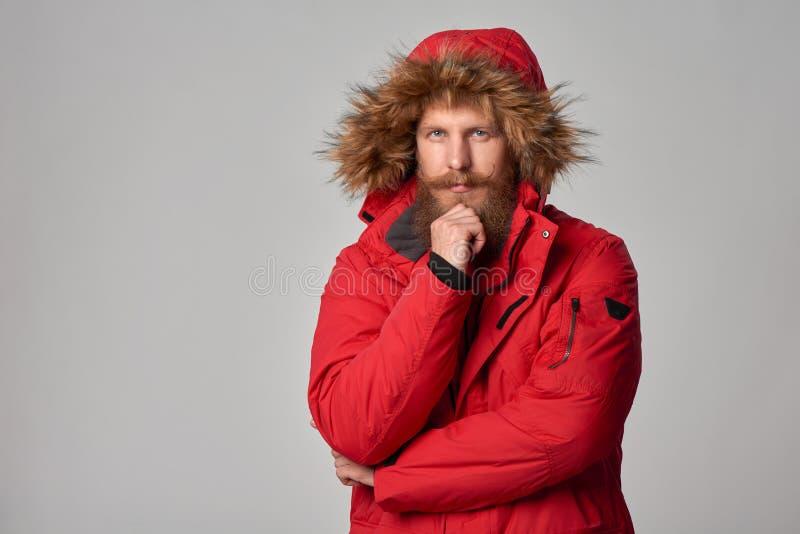 Σκεπτικό γενειοφόρο άτομο στο κόκκινο χειμερινό σακάκι στοκ φωτογραφίες με δικαίωμα ελεύθερης χρήσης