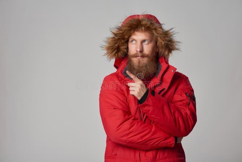 Σκεπτικό γενειοφόρο άτομο στο κόκκινο χειμερινό σακάκι στοκ φωτογραφίες