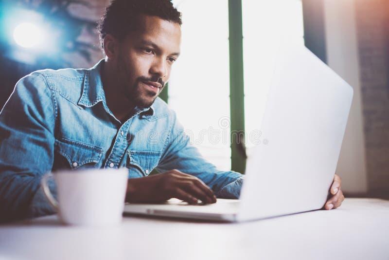Σκεπτικό γενειοφόρο αφρικανικό άτομο που εργάζεται στο lap-top ξοδεύοντας το χρόνο στο σπίτι Έννοια της νέας χρησιμοποίησης επιχε στοκ εικόνα