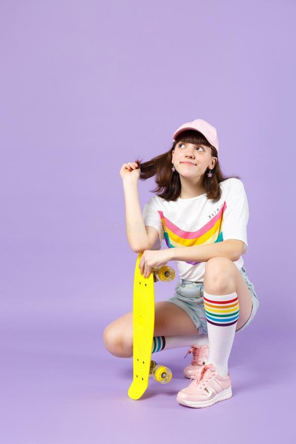 Σκεπτικό κορίτσι εφήβων στα ζωηρά ενδύματα που κάθεται κίτρινο skateboard εκμετάλλευσης, που φαίνεται επάνω απομονωμένο στον ιώδη στοκ εικόνα με δικαίωμα ελεύθερης χρήσης
