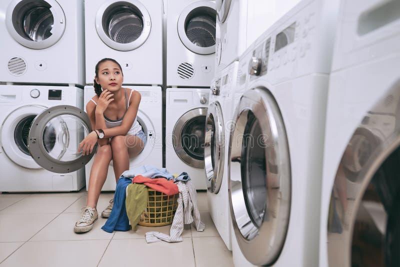 Σκεπτικό κορίτσι laundromat στοκ φωτογραφίες