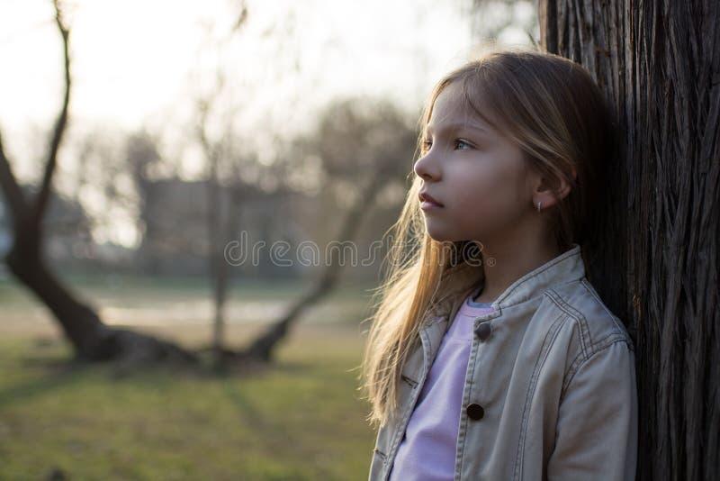 Σκεπτικό μικρό κορίτσι εκτός από ένα δέντρο στοκ εικόνες
