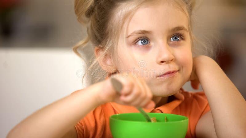 Σκεπτικό μικρό κορίτσι που έχει το πρόγευμα, διατροφή παιδικής ηλικίας, γεύμα νιφάδων καλαμποκιού στοκ φωτογραφία
