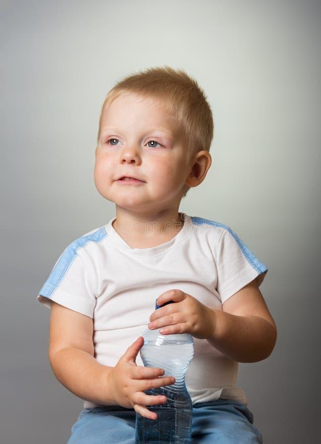 Σκεπτικό μικρό παιδί με ένα πλαστικό μπουκάλι του πόσιμου νερού στο γκρίζο υπόβαθρο στοκ φωτογραφίες με δικαίωμα ελεύθερης χρήσης