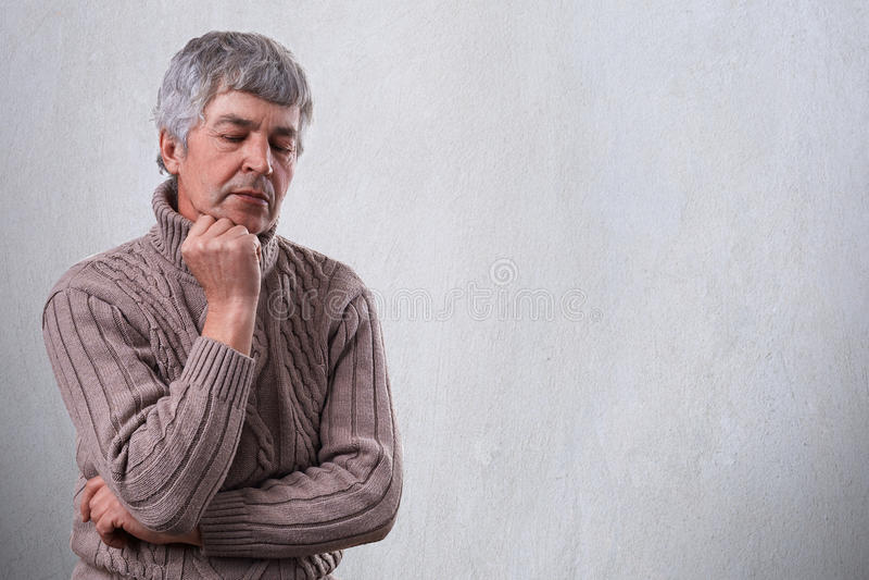 Σκεπτικό λυπημένο ώριμο άτομο που κρατά το χέρι του κάτω από το πηγούνι του που κοιτάζει κάτω με τη δυστυχισμένη έκφραση που σκέφ στοκ εικόνες με δικαίωμα ελεύθερης χρήσης