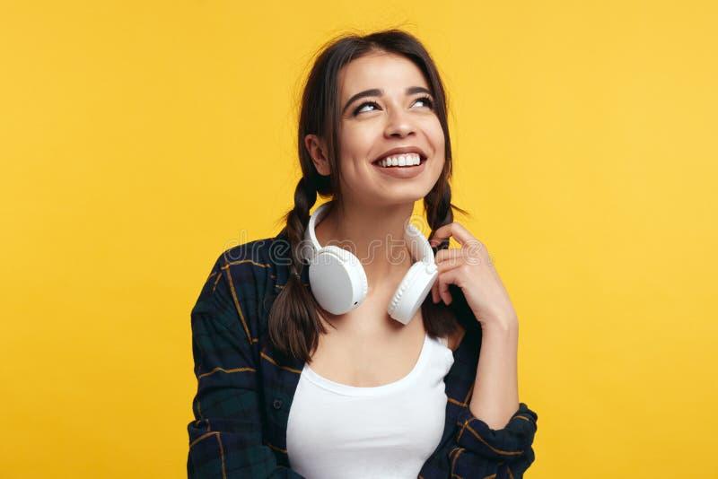 Σκεπτικό gilr χαμόγελου που φορά το μοντέρνο πουκάμισο και τα άσπρα ακουστικά που ανατρέχουν πέρα από τον κίτρινο τοίχο στοκ φωτογραφία