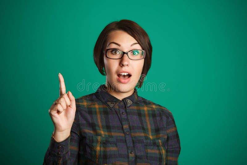 Σκεπτόμενη επιχειρησιακή γυναίκα με την ιδέα σχετικά με το πράσινο υπόβαθρο στοκ εικόνα με δικαίωμα ελεύθερης χρήσης
