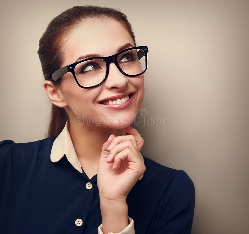 Σκεπτόμενη επιχειρησιακή γυναίκα που εξετάζει επάνω με το χέρι το πρόσωπο στοκ φωτογραφίες