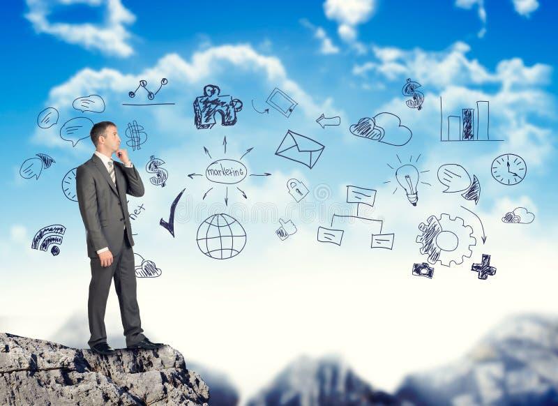Σκεπτόμενος επιχειρηματίας στην κορυφή βουνών στοκ εικόνα