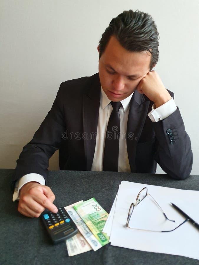 σκεπτόμενος νεαρός επιχειρηματίας που αναλύει τον προϋπολογισμό και τα χρήματα της Ρωσίας στο τραπέζι στοκ φωτογραφία με δικαίωμα ελεύθερης χρήσης