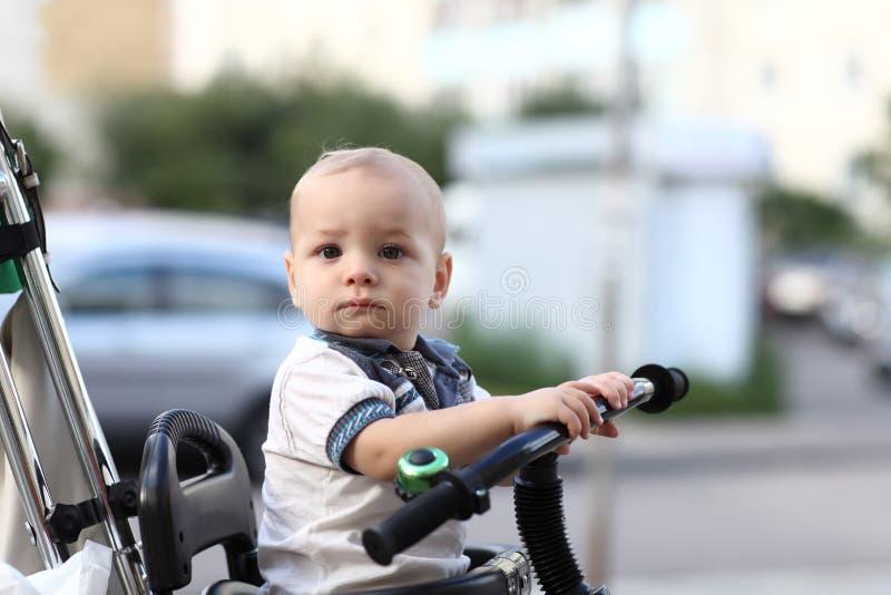 Σκεπτόμενο παιδί στο τρίκυκλο με την ώθηση handl στοκ εικόνες