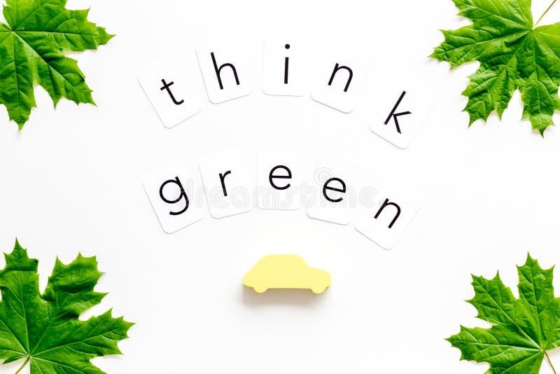 Σκεφτείτε την πράσινη έννοια με την άδεια σφενδάμνου και το αυτοκίνητο στην άσπρη τοπ άποψη υποβάθρου στοκ εικόνα