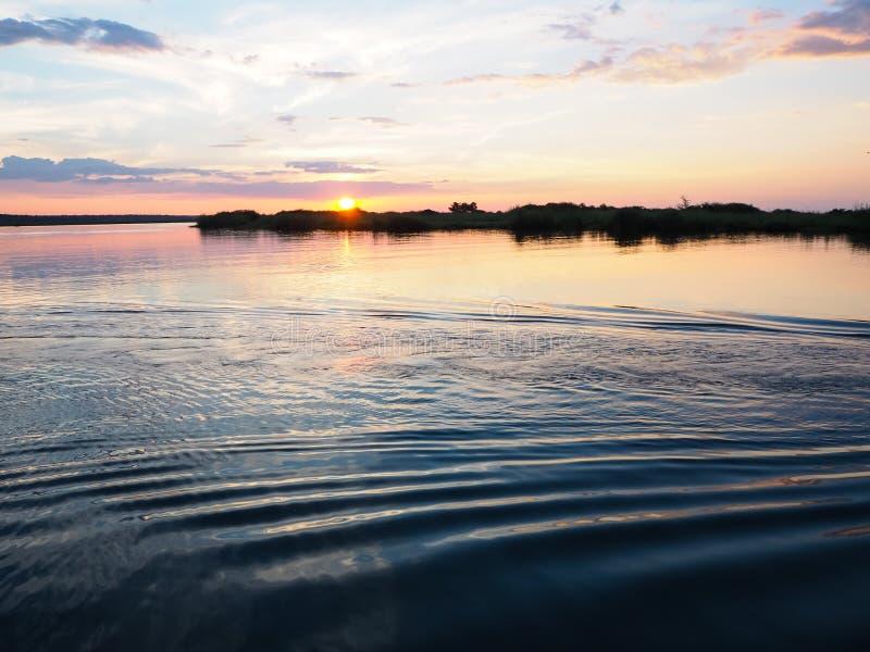 Σκηνή ηλιοβασιλέματος στην όχθη ποταμού με τον κυματισμό νερού και το γλυκό χρώμα στοκ εικόνες