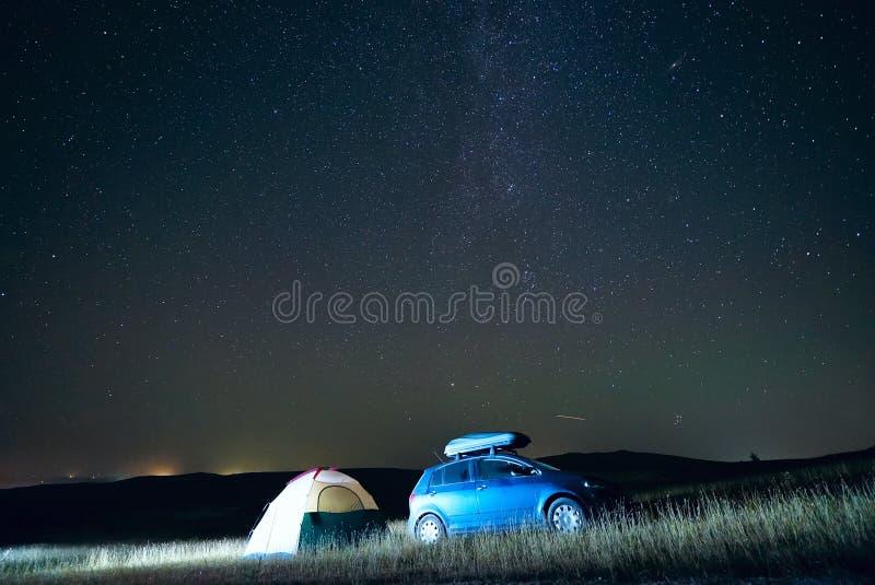 Σκηνή και αυτοκίνητο τουριστών τη νύχτα στο υπόβαθρο του γαλακτώδους τρόπου και του έναστρου ουρανού στοκ εικόνα