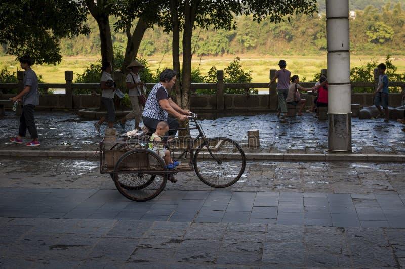 Σκηνή οδών στην πόλη Yangshuo με μια γυναίκα και ένα αγόρι σε ένα ποδήλατο στοκ εικόνα