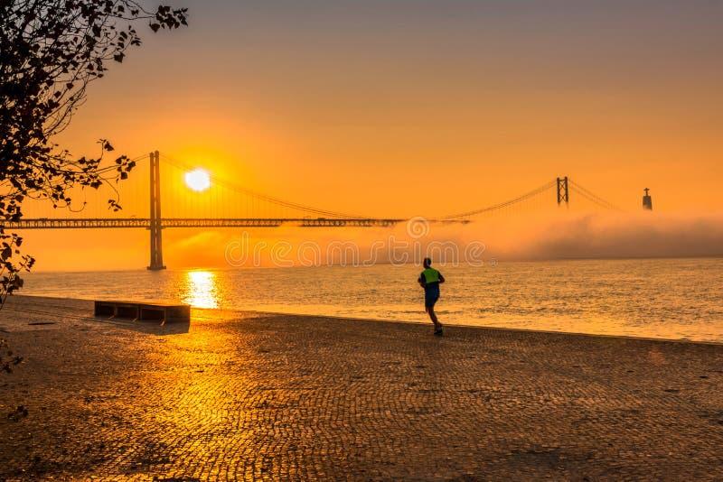 Σκηνή πόλεων με ένα άτομο που τρέχει στην πανέμορφη πορτοκαλιά ανατολή στοκ φωτογραφία με δικαίωμα ελεύθερης χρήσης
