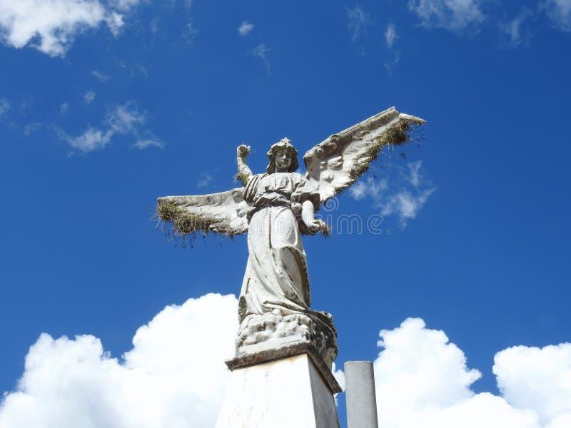 Σκηνή σε ένα νεκροταφείο: ένα παλαιό άγαλμα πετρών ενός αγγέλου με τα σπασμένα φτερά που βλέπουν από κάτω από στοκ εικόνα με δικαίωμα ελεύθερης χρήσης