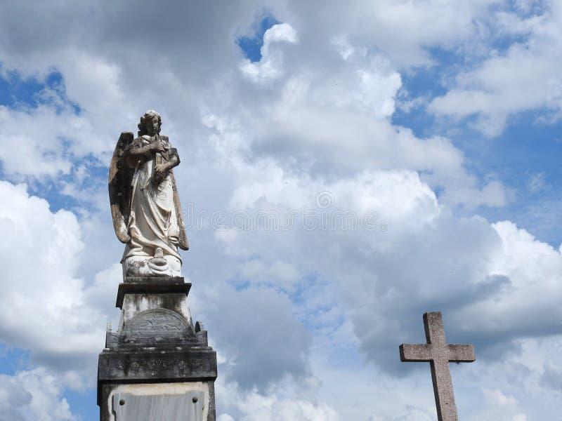 Σκηνή σε ένα νεκροταφείο: παλαιό άγαλμα πετρών ενός αγγέλου που κρατά έναν σταυρό Εκτός από το, ένας σταυρός πετρών στοκ φωτογραφίες
