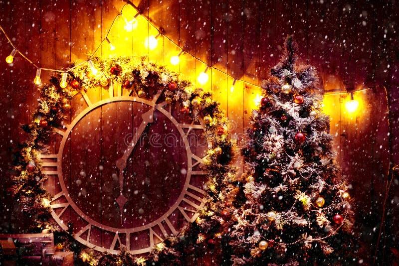 Σκηνή Χριστουγέννων με τα δώρα δέντρων και πυρκαγιά στο υπόβαθρο Παλαιό μεγάλο ρολόι οδών στον τοίχο του κτηρίου στοκ φωτογραφία