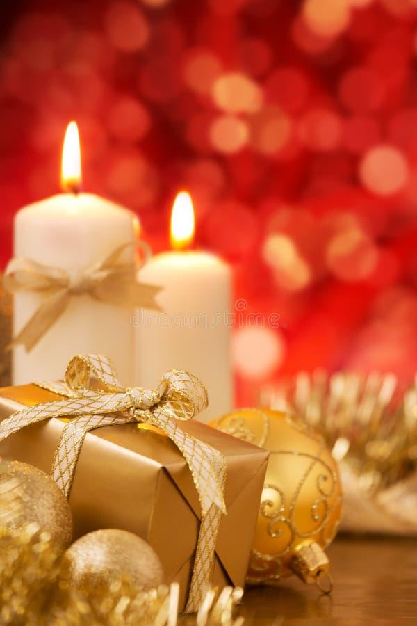 Σκηνή Χριστουγέννων με τα χρυσά μπιχλιμπίδια, το δώρο και τα κεριά, κόκκινο backgro στοκ εικόνες