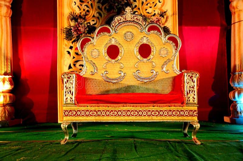 Σκηνική διακόσμηση δεξίωσης γάμου με τη χρυσή καρέκλα στοκ εικόνες