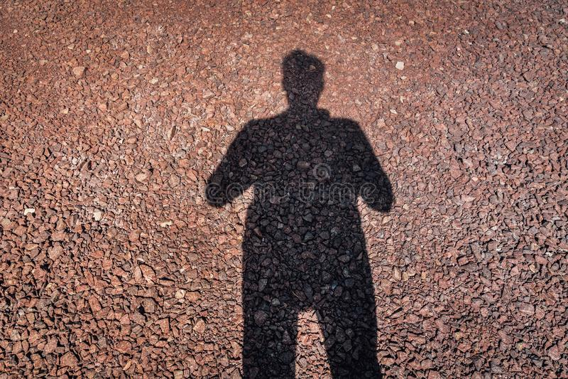 Σκιά ενός ατόμου σε ένα κόκκινο χαλίκι αλεσμένο με πέτρα στοκ φωτογραφία