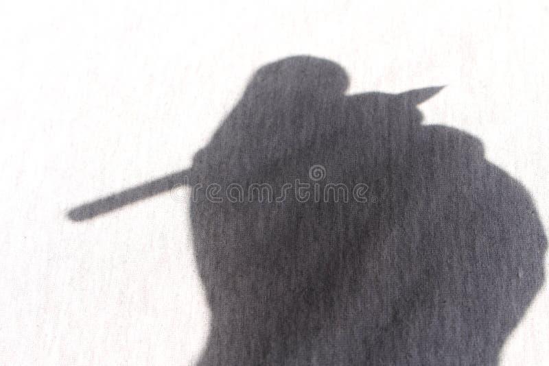 Σκιά ενός χεριού που γράφει με το κατασκευασμένο υπόβαθρο στοκ εικόνες