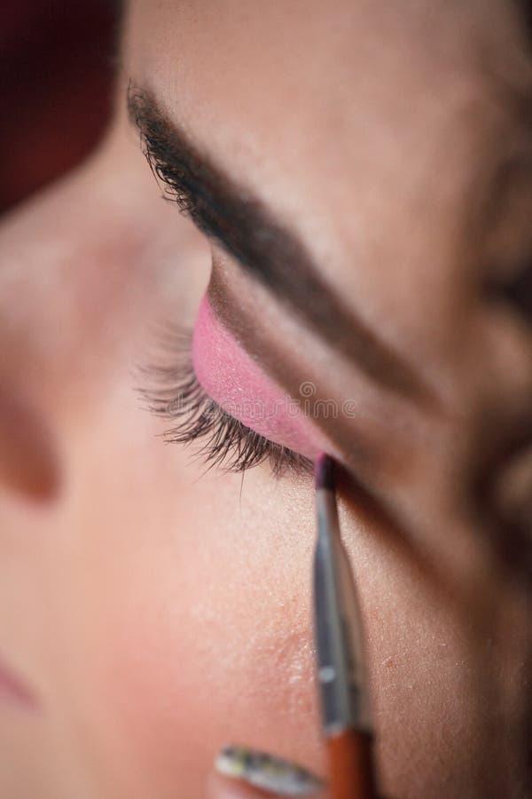 Σκιά ματιών που ισχύει, makeup για την κινηματογράφηση σε πρώτο πλάνο ματιών Η νέα γυναίκα εφαρμόζει τη ρόδινη χρωματισμένη σκιά  στοκ εικόνες