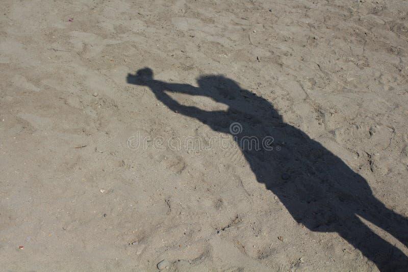 Σκιά του ατόμου που κάνει το δεμένο με χειροπέδες σημάδι στο υπόβαθρο άμμου στοκ φωτογραφία με δικαίωμα ελεύθερης χρήσης