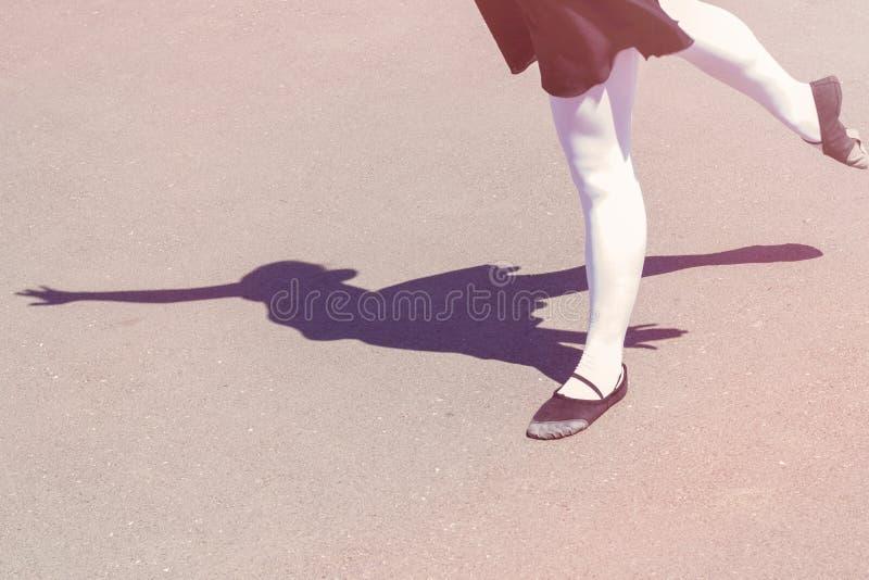 Σκιά του κοριτσιού χορευτών που κάνει τις κινήσεις χορού σε ένα κοστούμι λουσίματος για τα παπούτσια χορού και μπαλέτου στοκ εικόνα