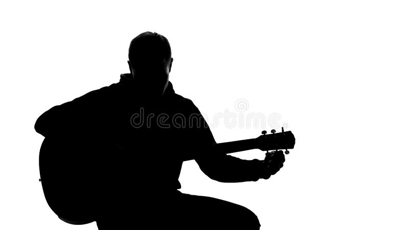 Σκιά του νέου μουσικού που συντονίζει επάνω την κιθάρα, επαγγελματικό τραγούδι γραψίματος, χόμπι στοκ εικόνες