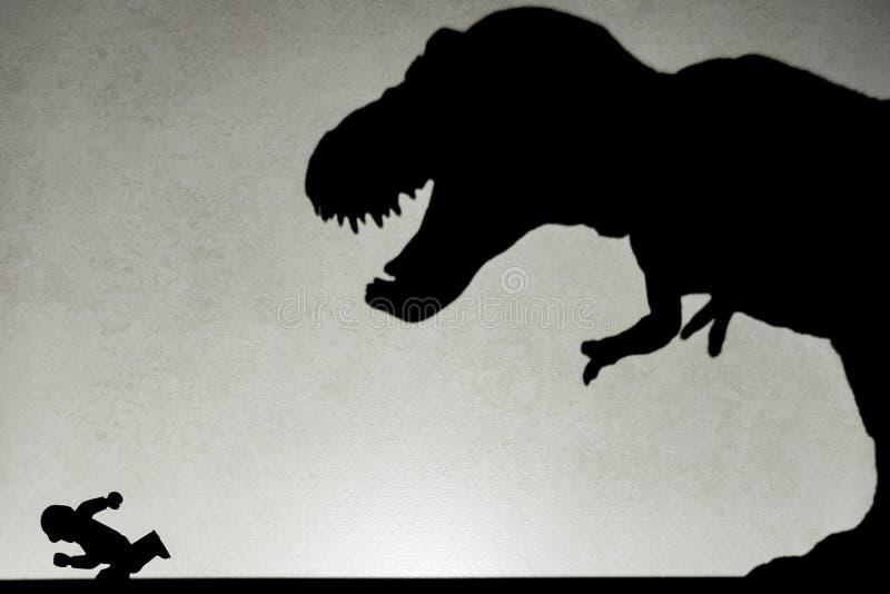 Σκιά του τυραννοσαύρου που χαράζει τον άνθρωπο στον τοίχο στοκ εικόνες