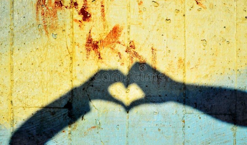 Σκιά των χεριών που διαμορφώνουν την καρδιά στοκ φωτογραφία