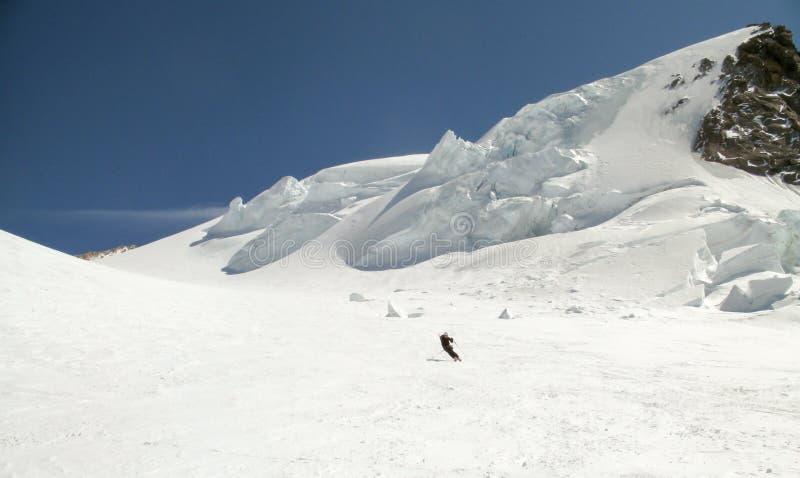 Σκιέρ πίσω χωρών που κάνει σκι κάτω από έναν τεράστιο αλπικό παγετώνα μια όμορφη χειμερινή ημέρα με την ένωση του πάγου seracs πί στοκ εικόνες με δικαίωμα ελεύθερης χρήσης