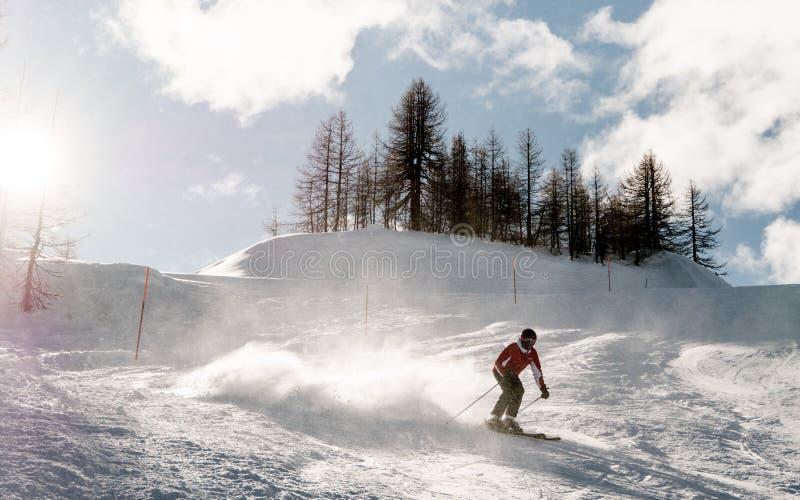 Σκιέρ που κάνει σκι προς τα κάτω κατά τη διάρκεια της ηλιόλουστης ημέρας στα υψηλά βουνά στοκ φωτογραφίες