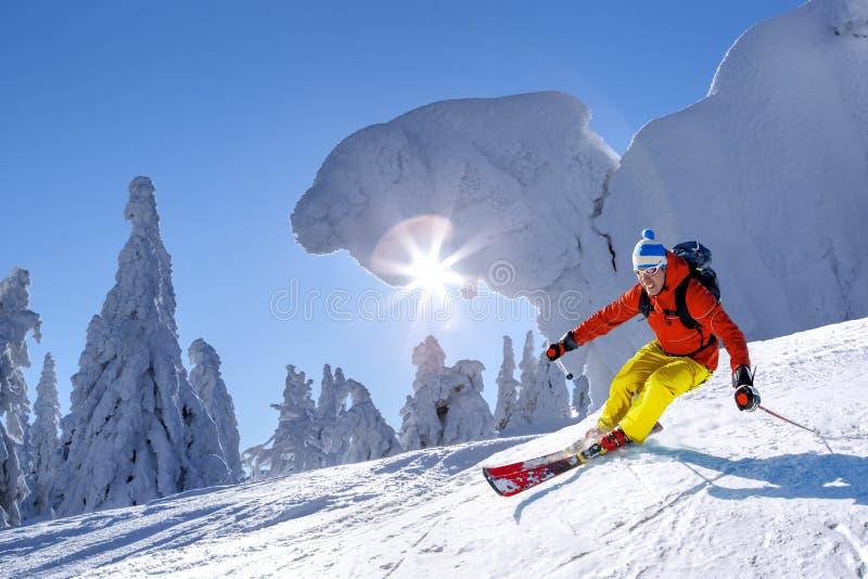 Σκιέρ που κάνει σκι προς τα κάτω στα υψηλά βουνά ενάντια στο μπλε ουρανό στοκ φωτογραφία