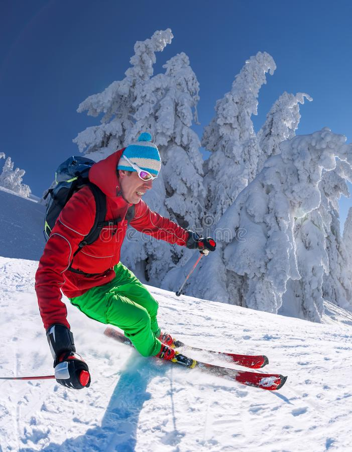 Σκιέρ που κάνει σκι προς τα κάτω στα υψηλά βουνά ενάντια στο μπλε ουρανό στοκ εικόνες με δικαίωμα ελεύθερης χρήσης