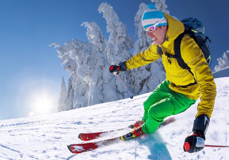 Σκιέρ που κάνει σκι προς τα κάτω στα υψηλά βουνά ενάντια στο μπλε ουρανό στοκ φωτογραφία με δικαίωμα ελεύθερης χρήσης