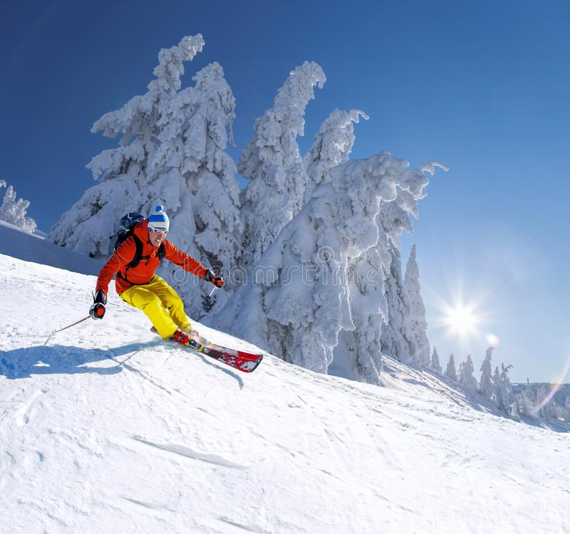 Σκιέρ που κάνει σκι προς τα κάτω στα υψηλά βουνά ενάντια στο μπλε ουρανό στοκ φωτογραφίες με δικαίωμα ελεύθερης χρήσης