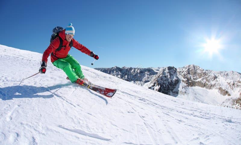 Σκιέρ που κάνει σκι προς τα κάτω στα υψηλά βουνά ενάντια στον ανελκυστήρα καλωδίων στοκ εικόνα με δικαίωμα ελεύθερης χρήσης