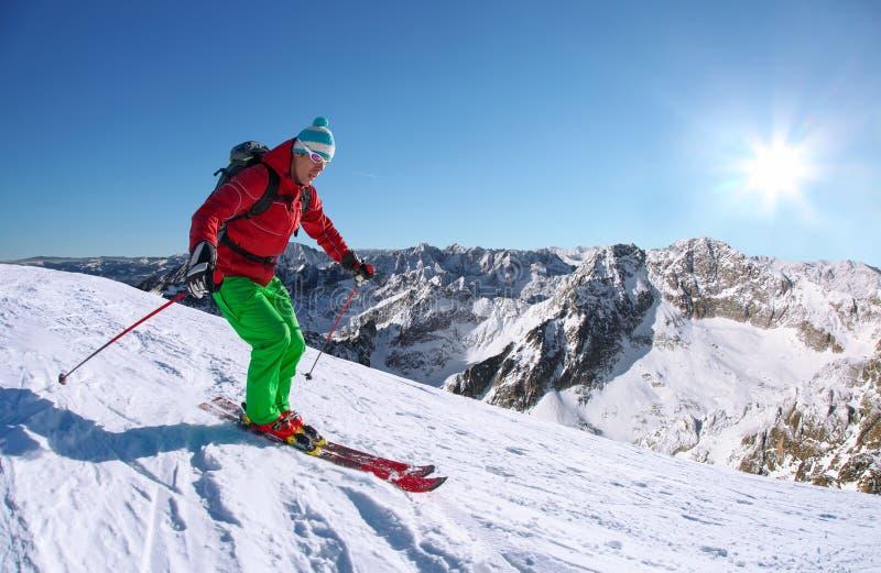 Σκιέρ που κάνει σκι προς τα κάτω στα υψηλά βουνά ενάντια στον ανελκυστήρα καλωδίων στοκ φωτογραφίες με δικαίωμα ελεύθερης χρήσης