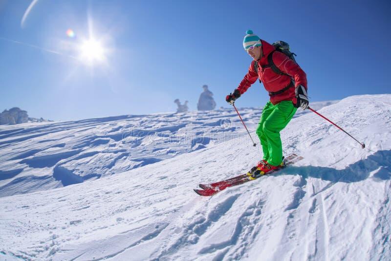 Σκιέρ που κάνει σκι προς τα κάτω στα υψηλά βουνά ενάντια στο ηλιοβασίλεμα στοκ εικόνες