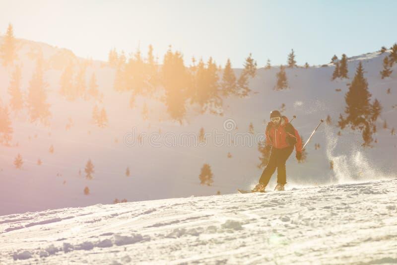 Σκιέρ που κάνει σκι προς τα κάτω στα υψηλά βουνά ενάντια στο ηλιοβασίλεμα στοκ εικόνες με δικαίωμα ελεύθερης χρήσης