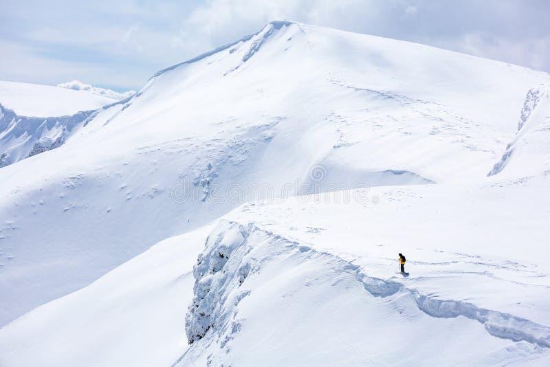 Σκιέρ που στέκεται στην κορυφή, χιόνι στοκ εικόνες