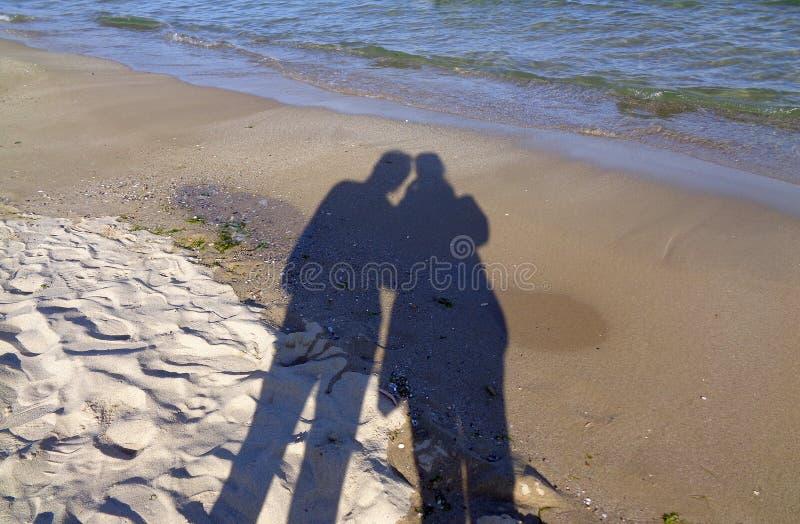 Σκιές ανδρών και γυναικών σε μια κρύα χειμερινή παραλία στοκ φωτογραφίες