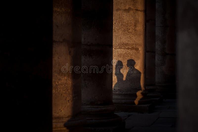 Σκιές του αγκαλιάσματος newlyweds στη στήλη του παλαιού κάστρου κατά τη διάρκεια του ηλιοβασιλέματος στοκ εικόνες με δικαίωμα ελεύθερης χρήσης