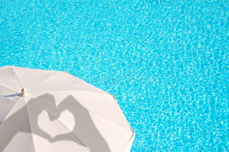 Σκιές των χεριών που διαμορφώνουν μια καρδιά άσπρο parasol, υπόβαθρο νερού πισινών, θερινή έννοια στοκ εικόνες