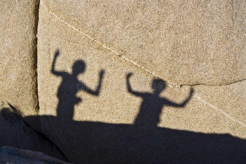Σκιές των χορεύοντας παιδιών σε έναν βράχο Jushua στο δέντρο Nationalpark στοκ εικόνες