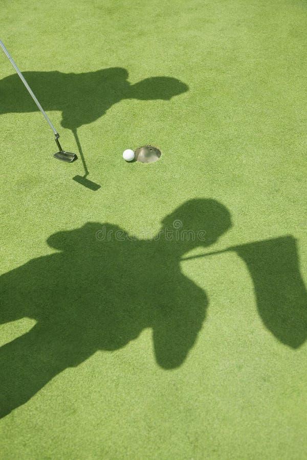 Σκιές δύο παικτών γκολφ που χτυπούν τη σφαίρα στο γήπεδο του γκολφ, σφαίρα στην τρύπα στοκ εικόνες
