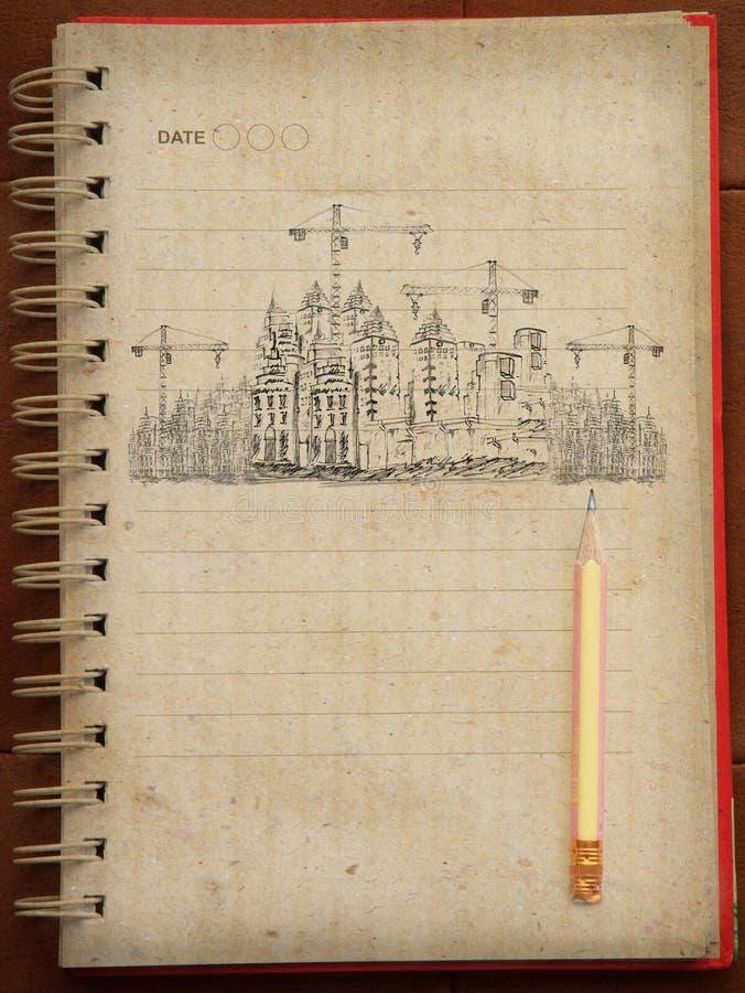Σκιαγράφηση της ιδέας για την οικοδόμηση κτηρίου στο βιβλίο σημειώσεων στοκ εικόνα